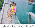 Portrait beautiful three young asian woman smiling happy wear the orange, yellow, pink bikini in relaxing sitting by swimming pool in hotel resort for leisure in vacation 76100521