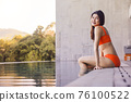 Portrait beautiful young asian woman smiling happy wear the orange bikini in relaxing sitting by swimming pool in hotel resort for leisure in vacation 76100522