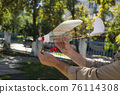 Airplane model with a propeller made from household waste plastic on a background of the sky in the hands of grandfather 76114308