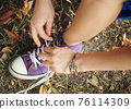 A girl ties white laces on lilac sneakers, close-up, against a background of grass and leaves, top view. 76114309