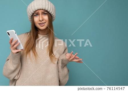 Closeup portrait Photo of beautiful dissatisfied young blonde woman wearing stylish beige warm 76114547