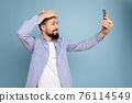 Handsome young brunet bearded man wearing casual stylish clothes standing isolated over blue 76114549