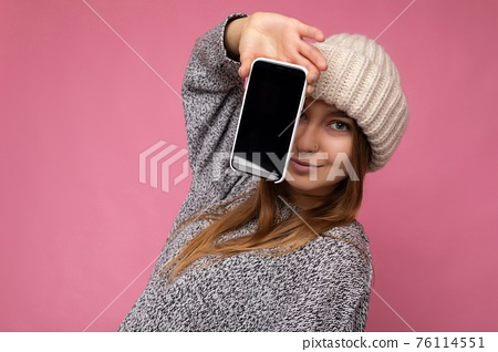 photo of Beautiful young blonde woman wearing casual grey sweater and beige hat isolated over pink 76114551