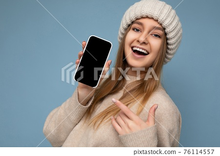 Closeup of beautiful positive young woman wearing stylish beige sweater and beige knitted winter hat 76114557
