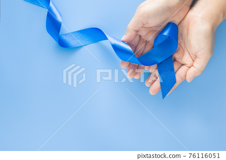 Hands holding deep blue ribbon on blue background with copy space. Colorectal Cancer Awareness Colon cancer of older person and world diabetes day Child abuse prevention. Healthcare, insurance concept 76116051