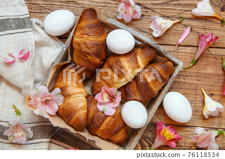 Fresh croissants, eggs and flowers  in a tray on a wooden table 76118534