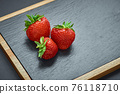 Strawberries on black stone board. Berries in the kitchen 76118710