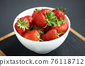 Strawberries on black background. Berries in a plate 76118712