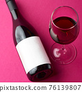 Wine Bottle with a blank label laying on its side and full wine glasses on pink background 76139807