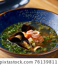 Delicious Seafood soup with seafood, shrimps and mussels on a wooden table 76139811