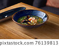 Delicious Seafood soup with seafood, shrimps and mussels on a wooden table 76139813