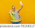 Man wearing underwater mask, striped shirt, swimming laps looking into the phone, taking very emotionally selfie while smiling on yellow background. Vacation concept 76158317
