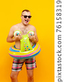 Adult topless man in rubber ring form of snail and sunglasses posing on yellow background. Isolate 76158319