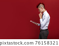 Side view of red-haired teen punk with tablet against of red background. Isolated 76158321