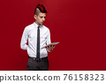 Elegant punk with tablet against of red background 76158323