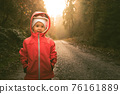 Child standing on wet path in moody forest. 76161889