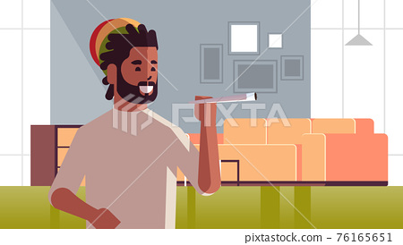 african american guy smoking cannabis marijuana joint drug consumption concept modern living room interior portrait horizontal 76165651