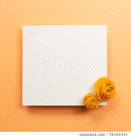 Blank memo pad with dry flowers on orange background. top view, copy space 76168341