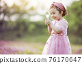 Little girl playing on the park lawn 76170647