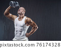 Fit man at workout in gym with shaker 76174328