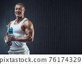 Fit man at workout in gym with shaker 76174329