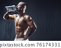 Fit man at workout in gym with shaker 76174331