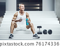Fit man at workout in gym with cell phone 76174336