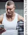Fit man at workout in gym with cell phone 76174338