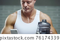 Fit man at workout in gym with cell phone 76174339