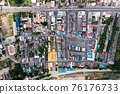 Crowded commercial building and residential in rural neighborhood and traffic on road 76176733