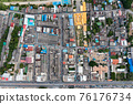 Crowded commercial building and residential in rural neighborhood and traffic on road 76176734
