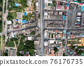 Crowded commercial building and residential in rural neighborhood and traffic on road 76176735