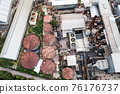 Ethanol industrial or biofuel refinery processing factory with smoke from chimney, storage tanks and warehouse 76176737