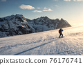 Backpacker man hiking and taking a photo on snow mountain with sunlight shine in the sunset at Lofoten Islands 76176741