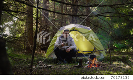 A man near a fire in the forest 76178153