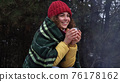 Young woman drinks tea by the fire in the winter forest 76178162
