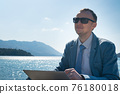 freelancer businessman working remotely on laptop while sitting on the pier 76180018