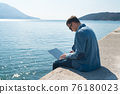 freelancer businessman working remotely on laptop while sitting on the pier 76180023