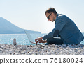 freelancer businessman working remotely on laptop at the beach near the zen pyramid 76180024