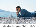 a man in a jacket lies on the beach and looks at the zen pyramid 76180027