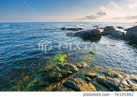 sea coast scenery in the morning. boulders in the calm water. few clouds on the sky in forenoon light. lonely place for summer vacations. sunny weather 76185802