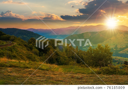 mountainous rural landscape at sunset. grassy meadow on top of a hill. clouds above the ridge in evening light. view in to the distant valley 76185809