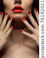 Beautiful girl showing red manicure nails . makeup and cosmetics. Brunette girl with long and shiny curly hair 76192021
