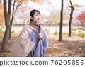 一個感覺秋天到來並尋找秋天葉子的女人 76205855