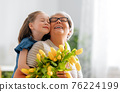 Grandma and girl smiling and hugging 76224199