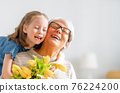 Grandma and girl smiling and hugging 76224200