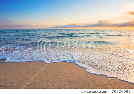 summer vacation at the seaside. beautiful seascape at sunrise. calm waves wash the golden sandy beach. fluffy clouds on the sky 76226098