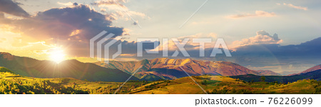 mountainous rural panorama landscape in springtime at sunset. beautiful scenery beneath a sky with clouds in evening light. grass covered hill rolling in to the distant ridge 76226099