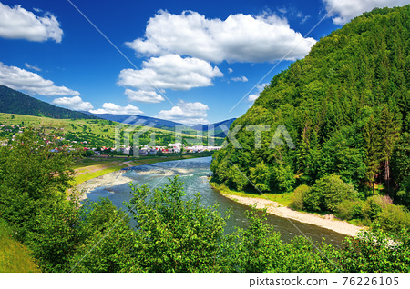 river runs through mountain valley. beautiful summer countryside landscape. village in the distance. wonderful scenery view. fluffy clouds on the deep blue sky 76226105