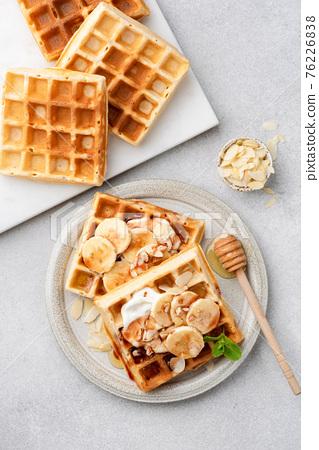 Sweet belgian waffles with cream, banana and honey 76226838